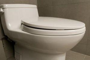 Comment remplacer un toilettes Quatre-Bolt Avec un toilettes Deux-Bolt sur un plancher de tuiles